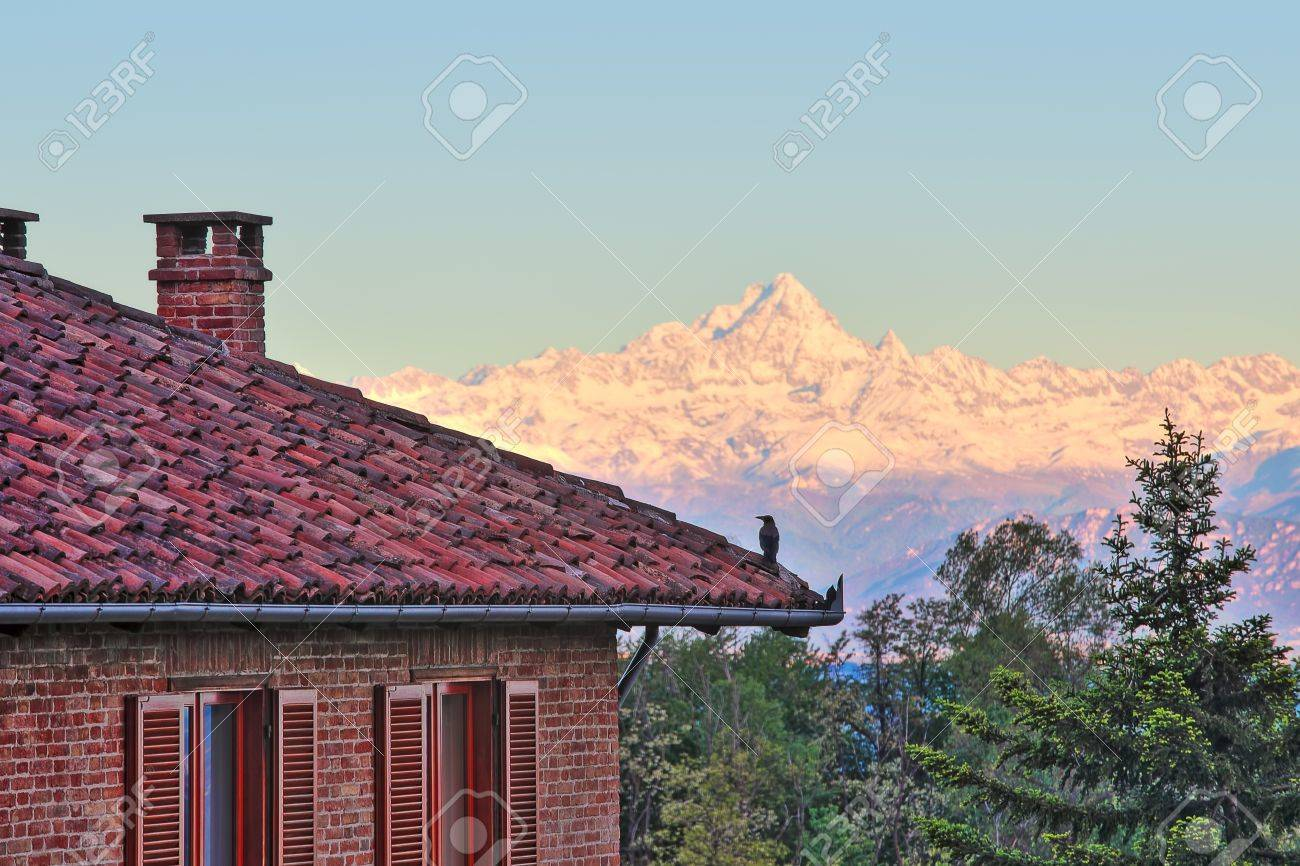 Lovely Red Brick House With Tiled Roof And Snowy Peaks Of Monviso Mountain Part Of  Italian Alps