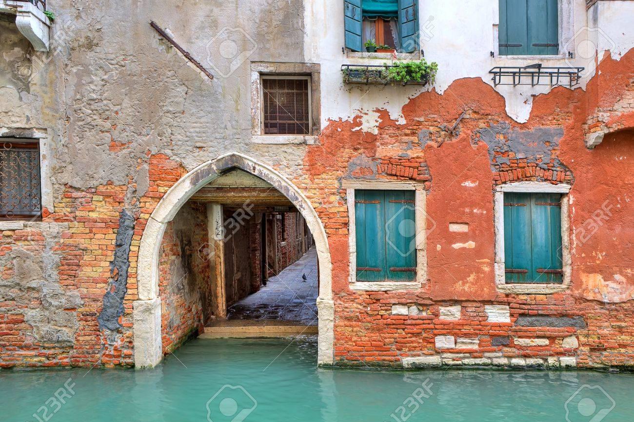 Smal kanaal en de gevel van de oude rode bakstenen huis met