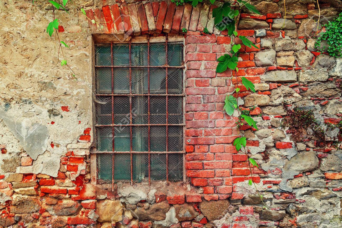 Fragment Of Old Abandoned Brick House With Closed Window Behind Iron Bars  In Small Italian Town