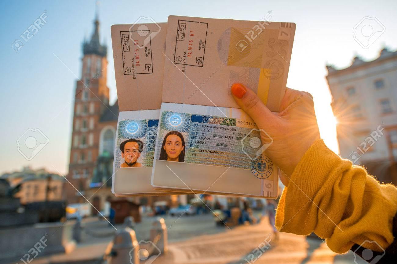 Elegant Frau übergibt Holding Ukrainische Pässe Mit Schengen Visa Auf Dem  Stadtzentrum Von Krakau Hintergrund.