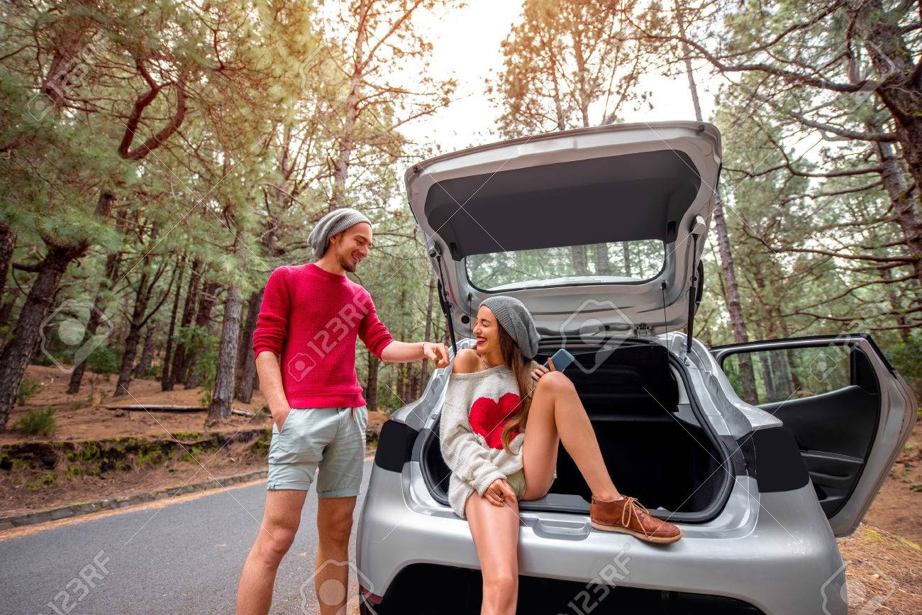 Pretty Couple In Sweaters And Hats Sitting In The Car Trunk On