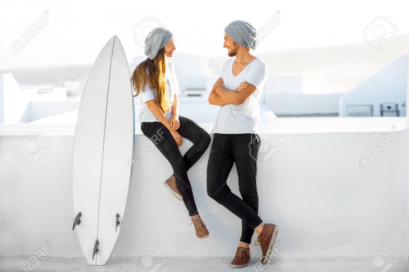 Pareja De Jóvenes Vestidos Igual En Las Camisetas Blancas Y Sombreros Que Disfrutan De Las Vacaciones De Verano Con La Tabla De Surf En La Parte