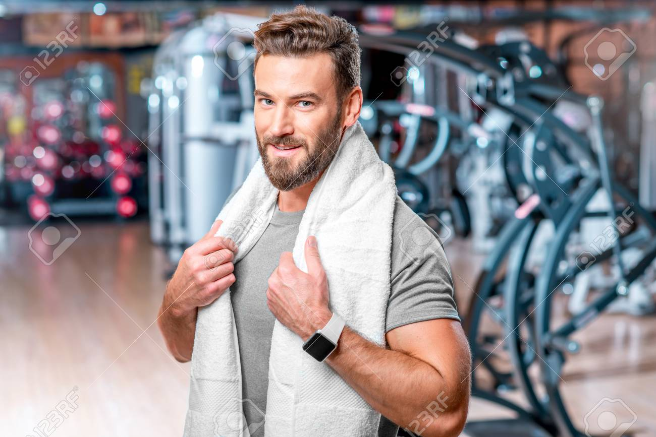 Lifestyle portrait of handsome muscular man standing with towel after the  training in the sport gym 703345e67