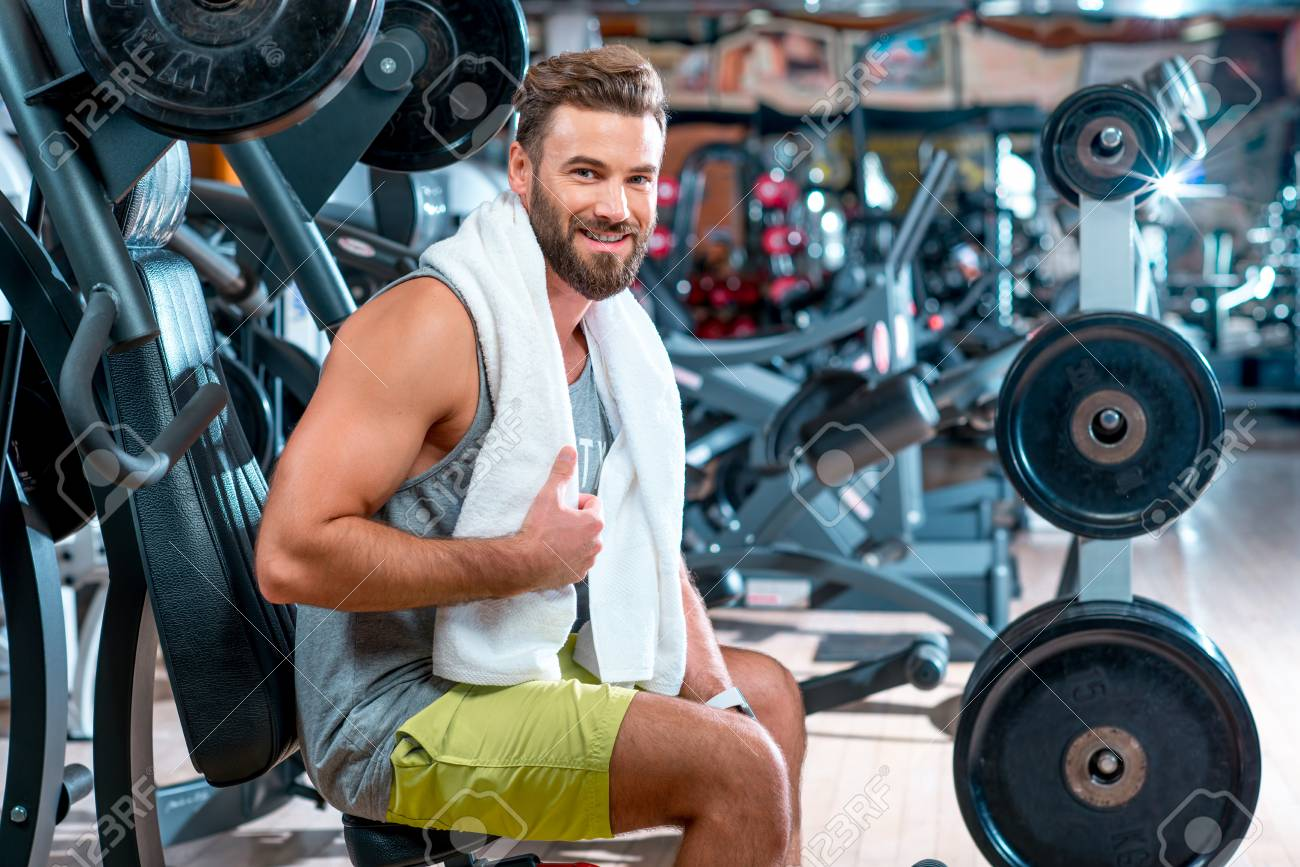 Lifestyle portrait of handsome muscular man with towel sitting on the  simulator in the gym Stock dae4c8037