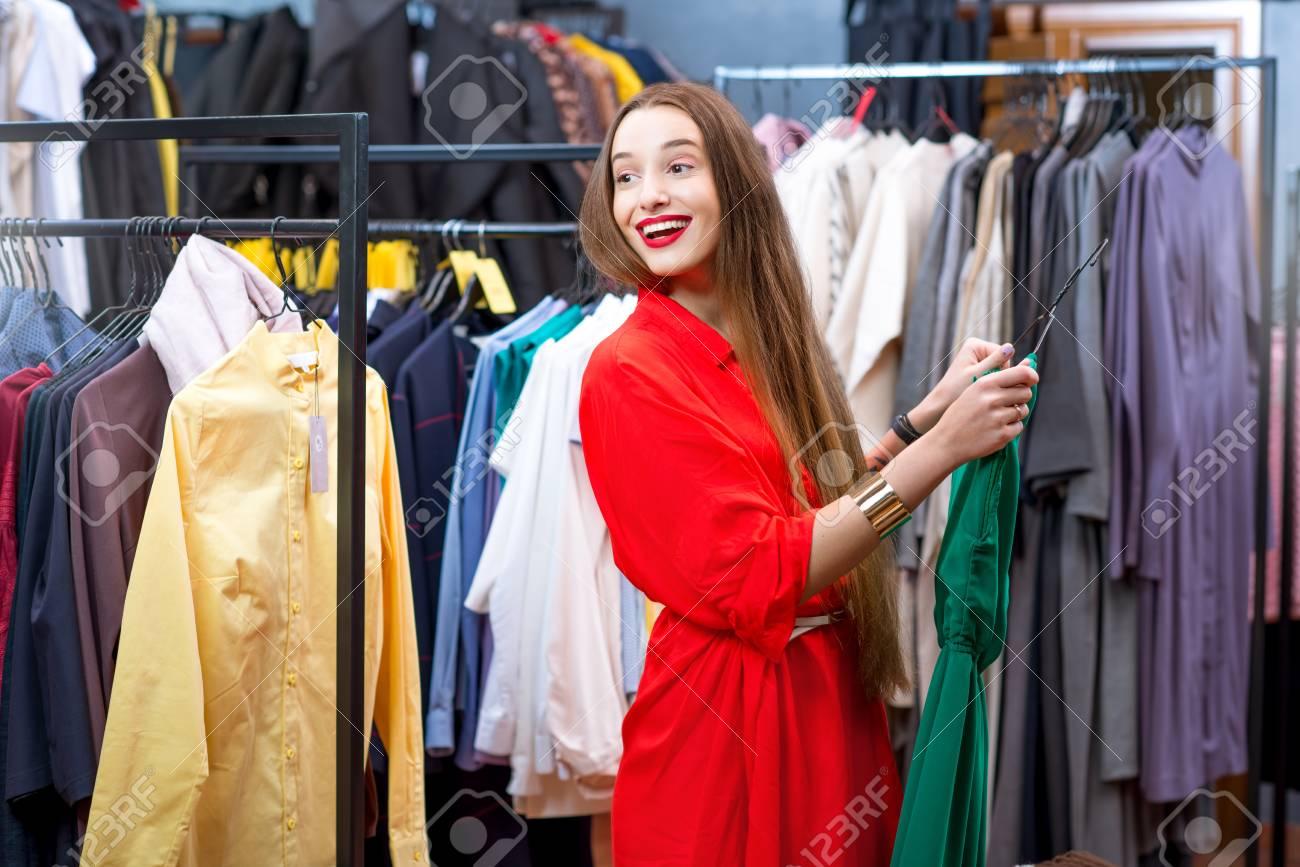 ab52a772ca Banque d'images - Jeune femme à la robe rouge, faire du shopping dans le  magasin de vêtements de luxe