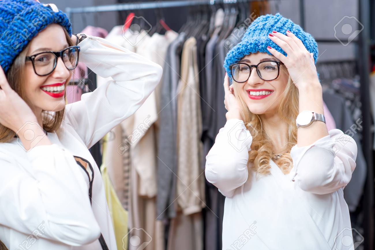 7476fed84 Two beautiful women trying blue hats in the clothing store. Happy winter  shopping Stock Photo
