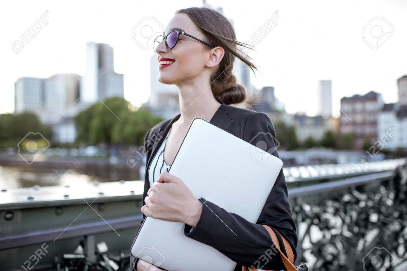 Businesswoman with laptop outdoors - 80689163
