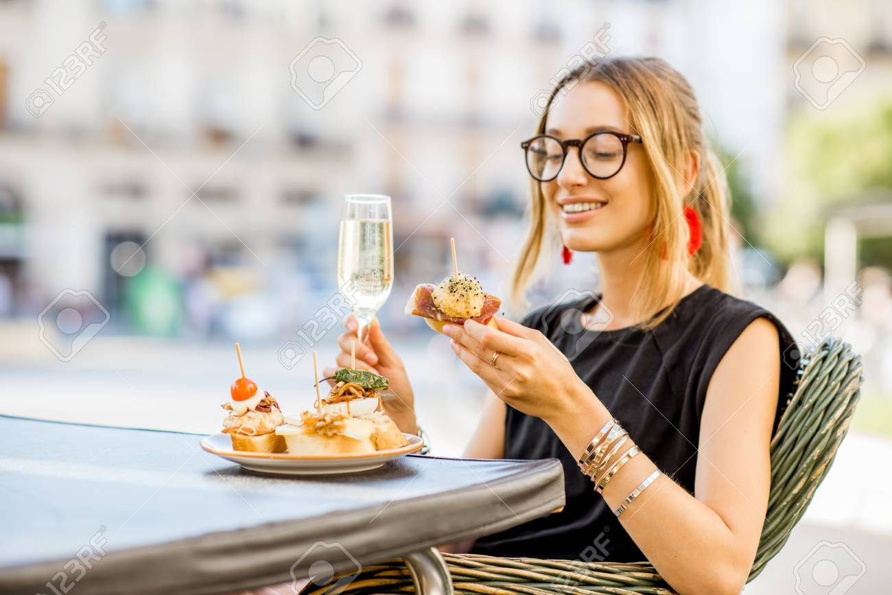 Young woman enjoying tasty appetizer with pinchos, traditional spanish snack, with glass of wine sitting outdoors at the bar in Valencia city - 88580666