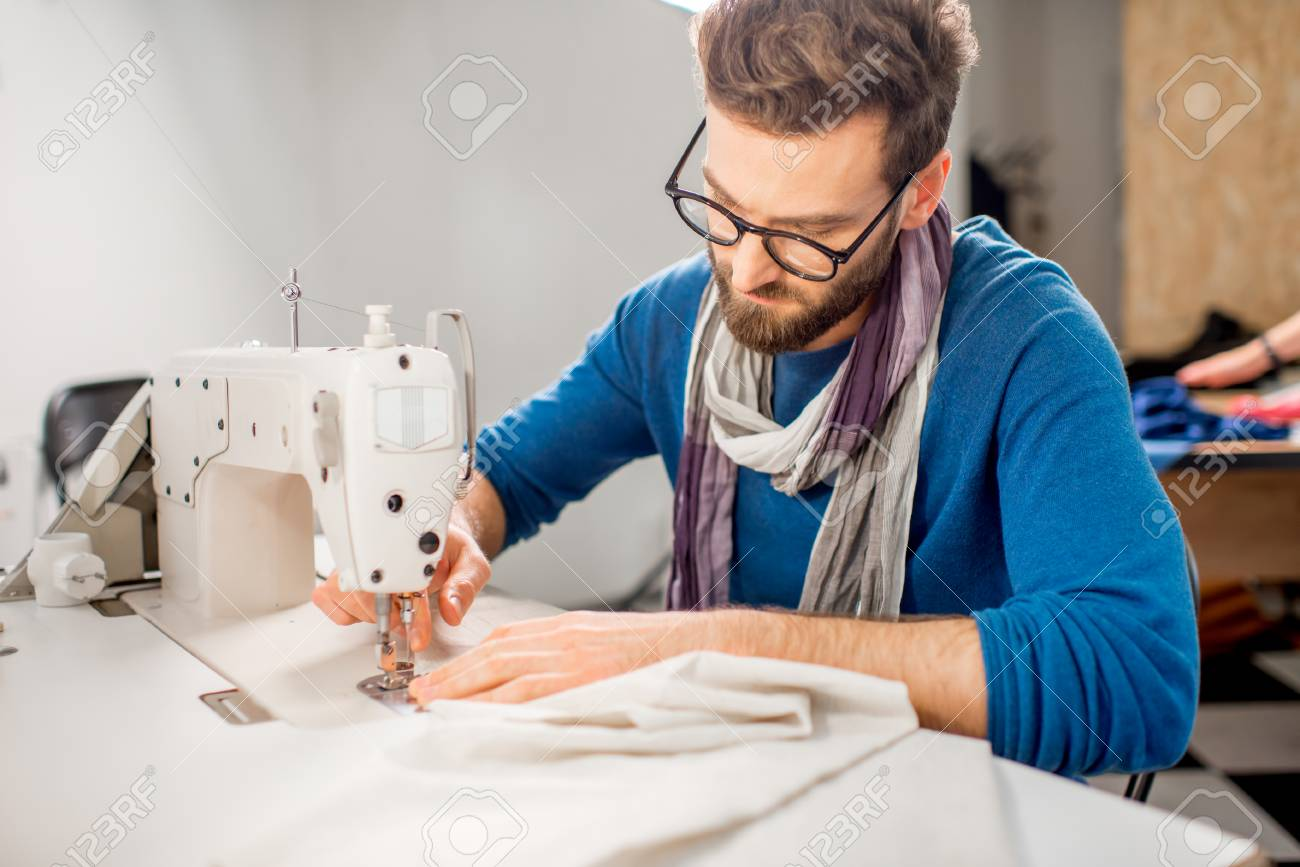 Handsome tailor sewing fabric with a sewing machine at the studio - 92357368