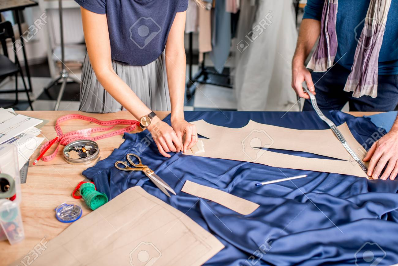 Cutting blue fabric on the table full of tailoring tools. Close-up view on the hands and fabric with no face - 92357478