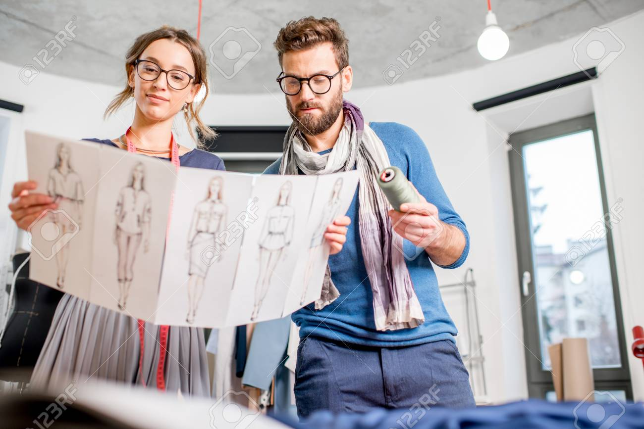 Couple of fashion designers working with clothing sketches at the studio - 92357541