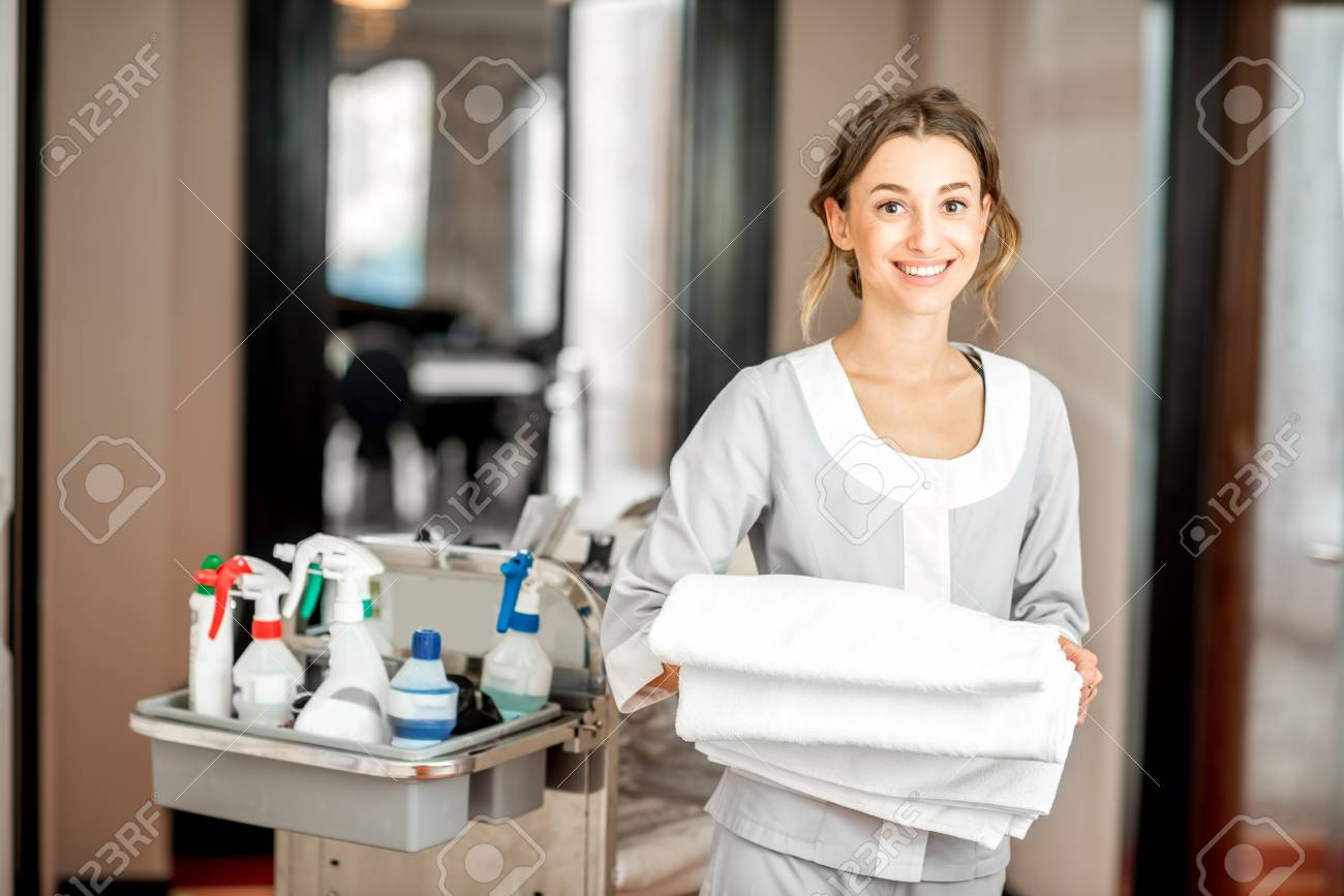 Portrait of a young woman chambermaid holding a towel standing with maid cart full of cleaning stuff in the hotel corridor - 95037622
