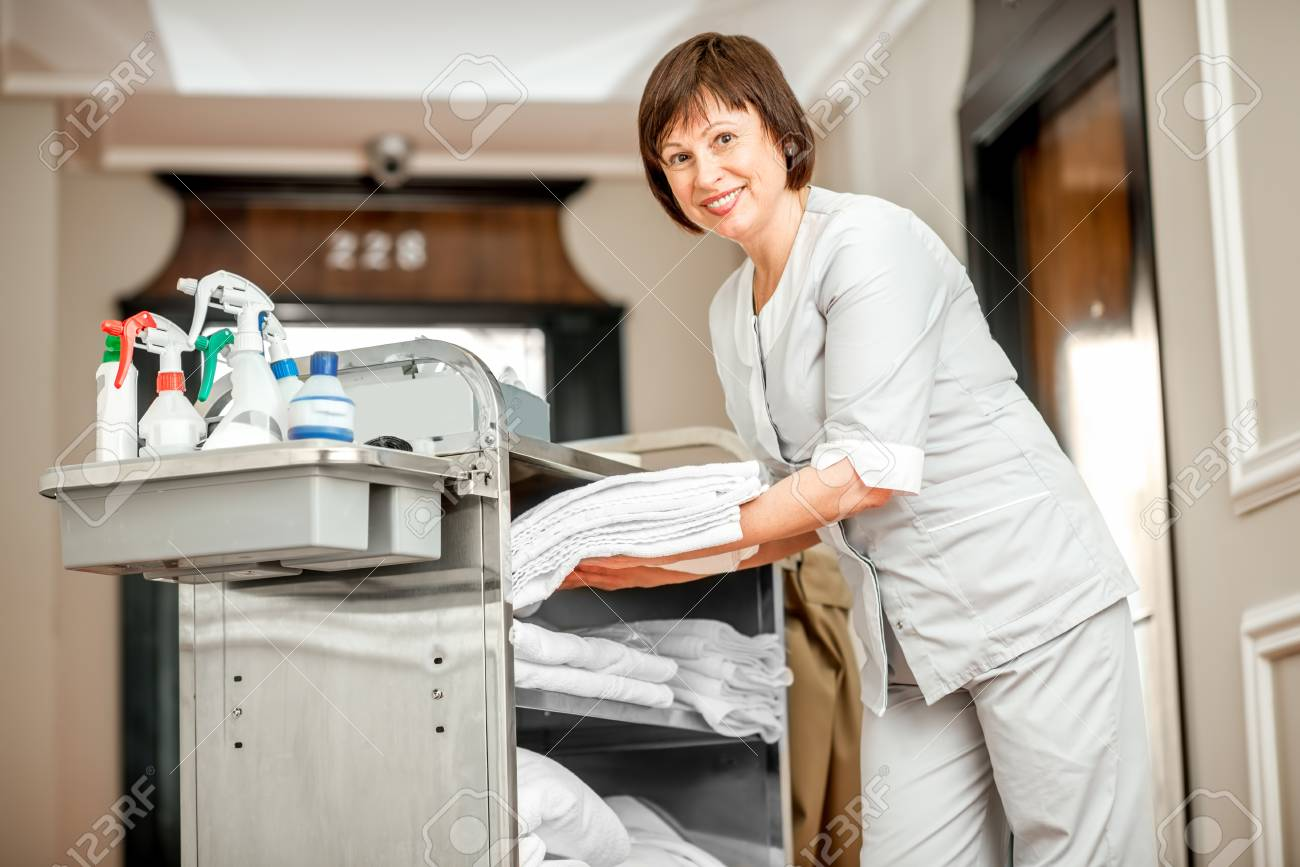 Senior woman chambermaid taking a clean towels from maid cart full of cleaning stuff in the hotel corridor - 95253293