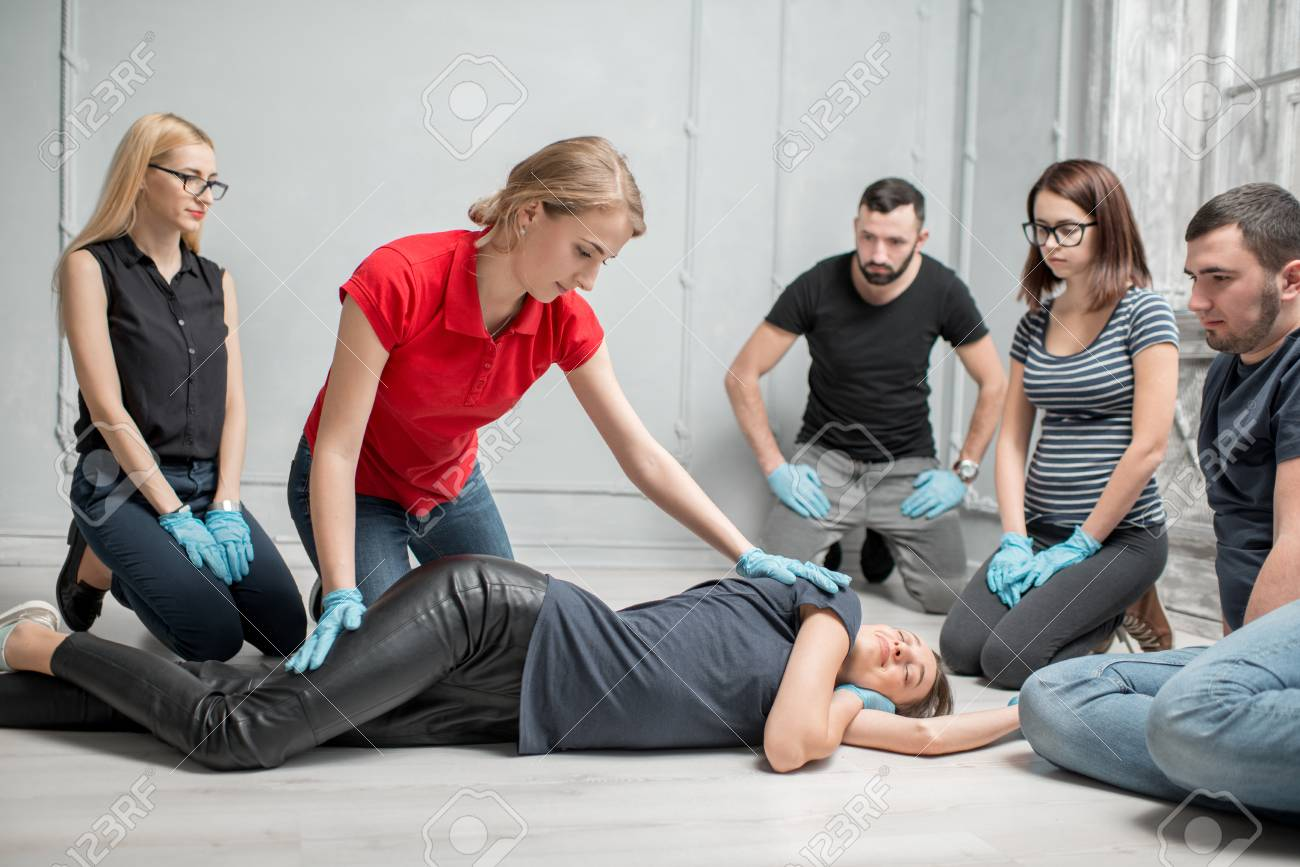 Young woman instructor showing how to lay down a woman during the first medical aid training indoors - 97864859