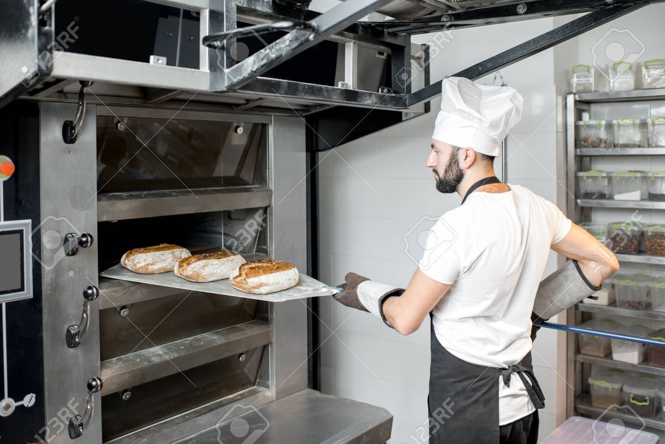 Baker taking off baked breads with shovel from the professional oven at the manufacturing - 97853766