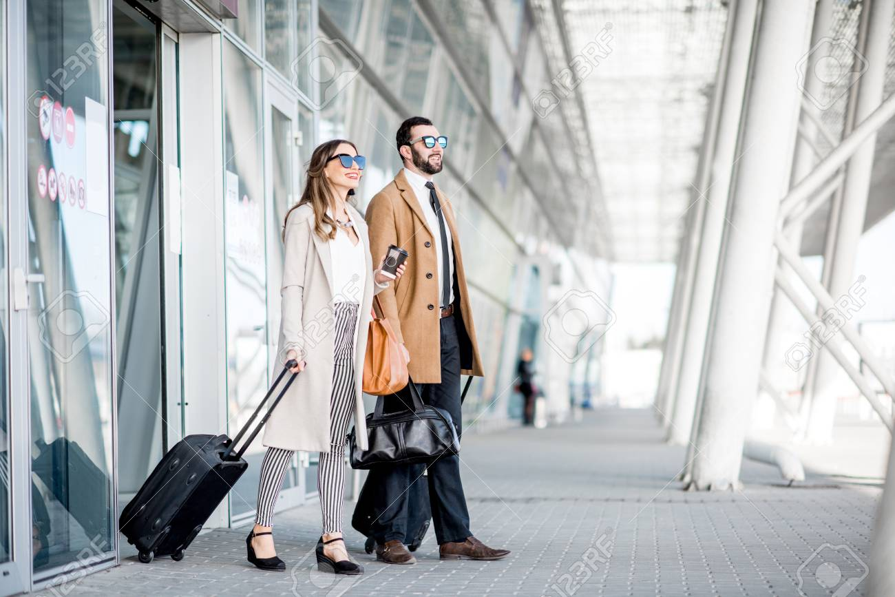 Business couple in coats walking out the airport with luggage during the business trip - 101098967