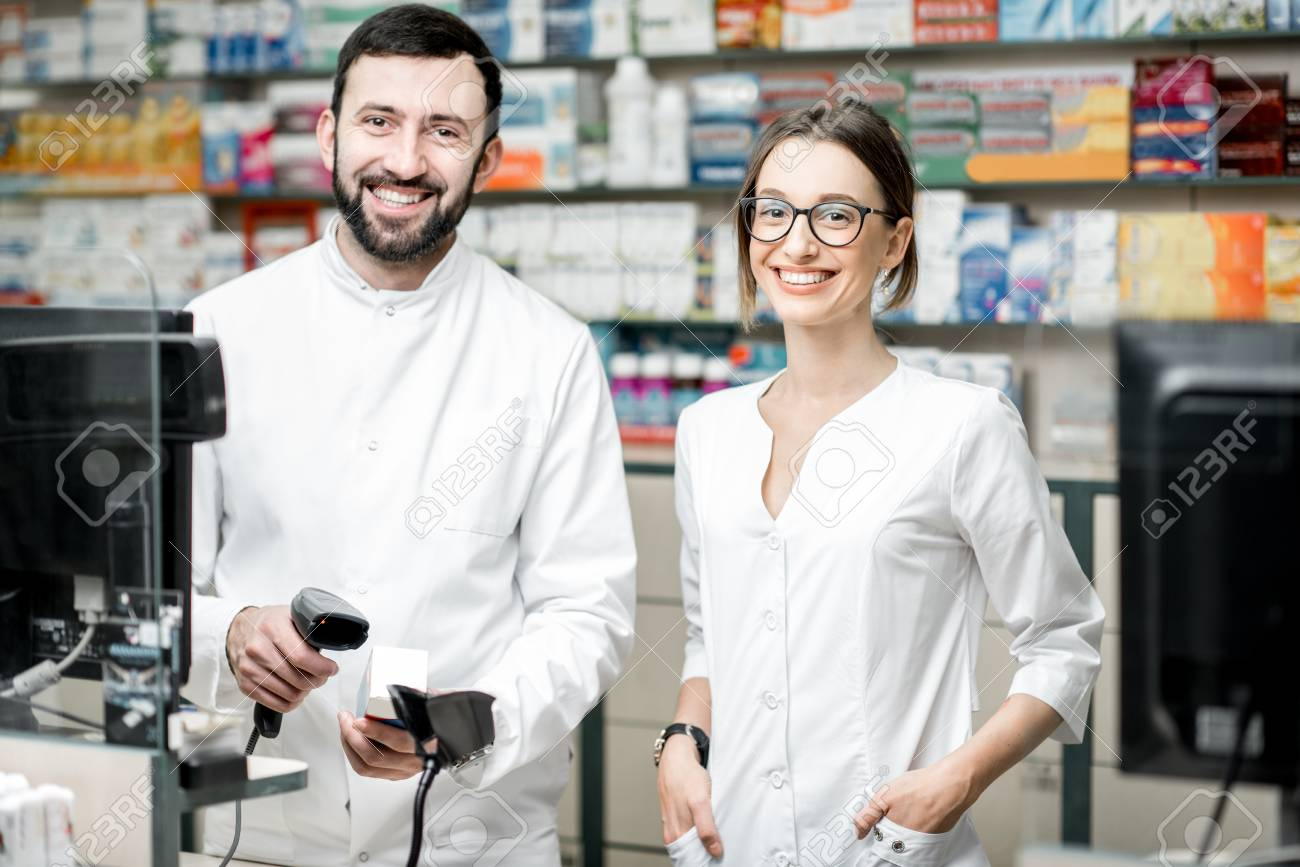 Portrait of a two pharmacists working at the paydesk selling medications in the pharmacy store - 100136590
