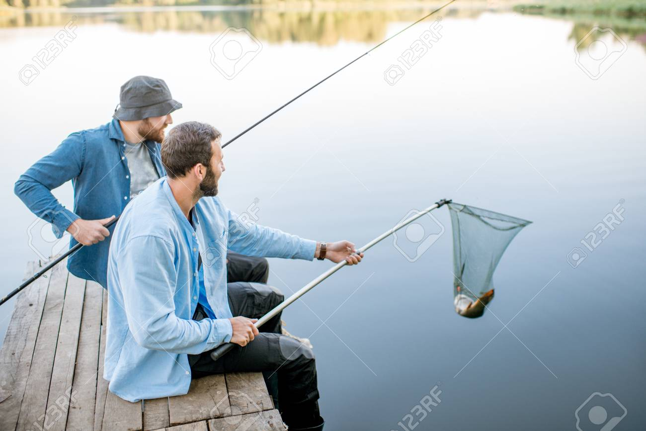 Two Friends Catching Fish With Fishing Net And Rod Sitting On