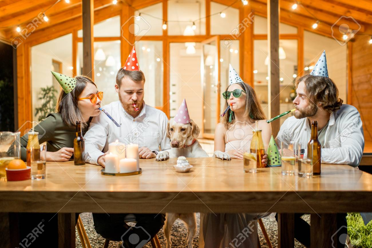Friends celebrating dogs birthday with cake at the table on the backyard of the house in the evening - 105233922