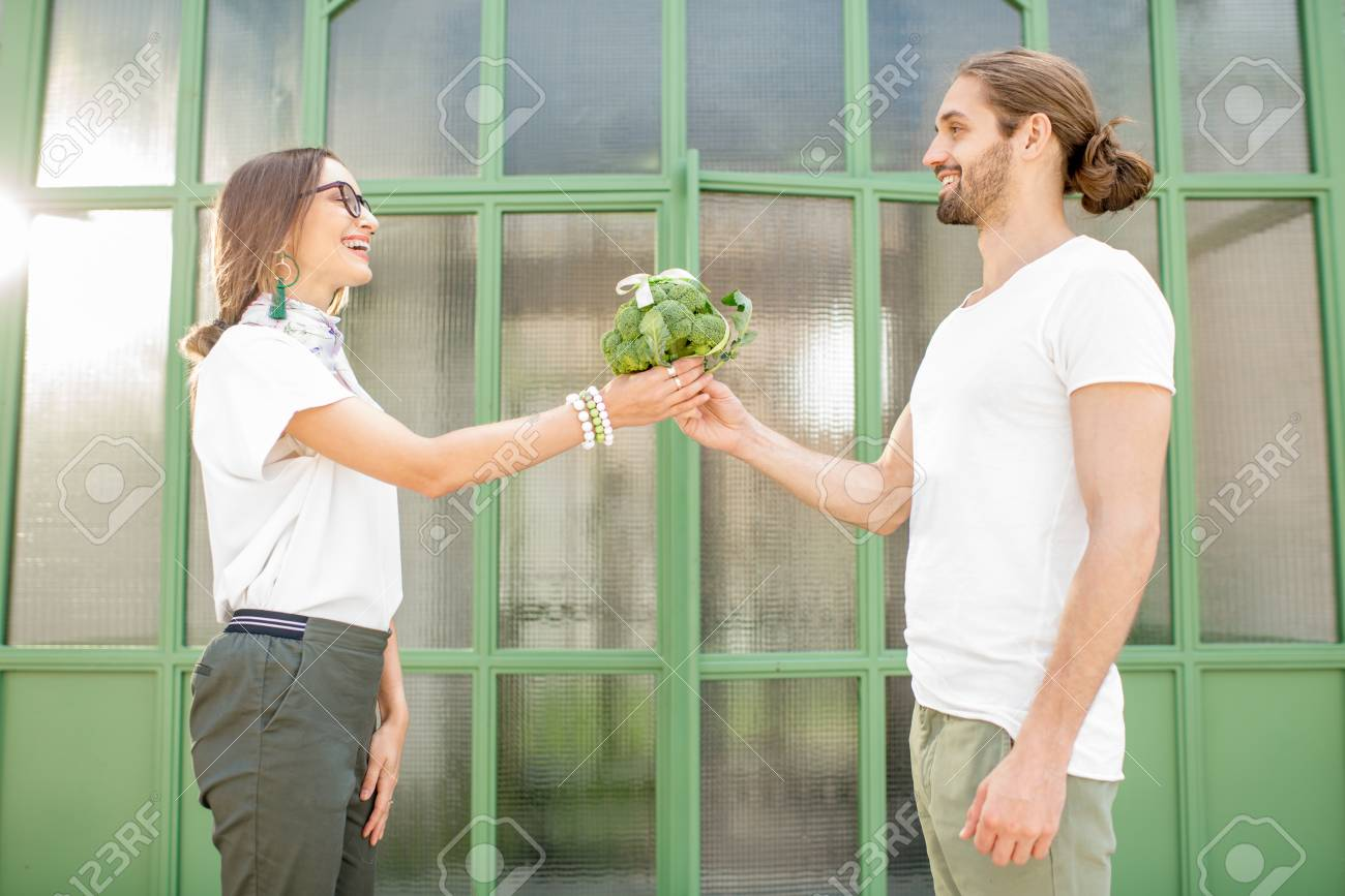104991330-man-giving-to-a-woman-fresh-bunch-of-broccoli-tied-in-a-bow-as-a-gift-outdoors-on-the-green-backgrou.jpg