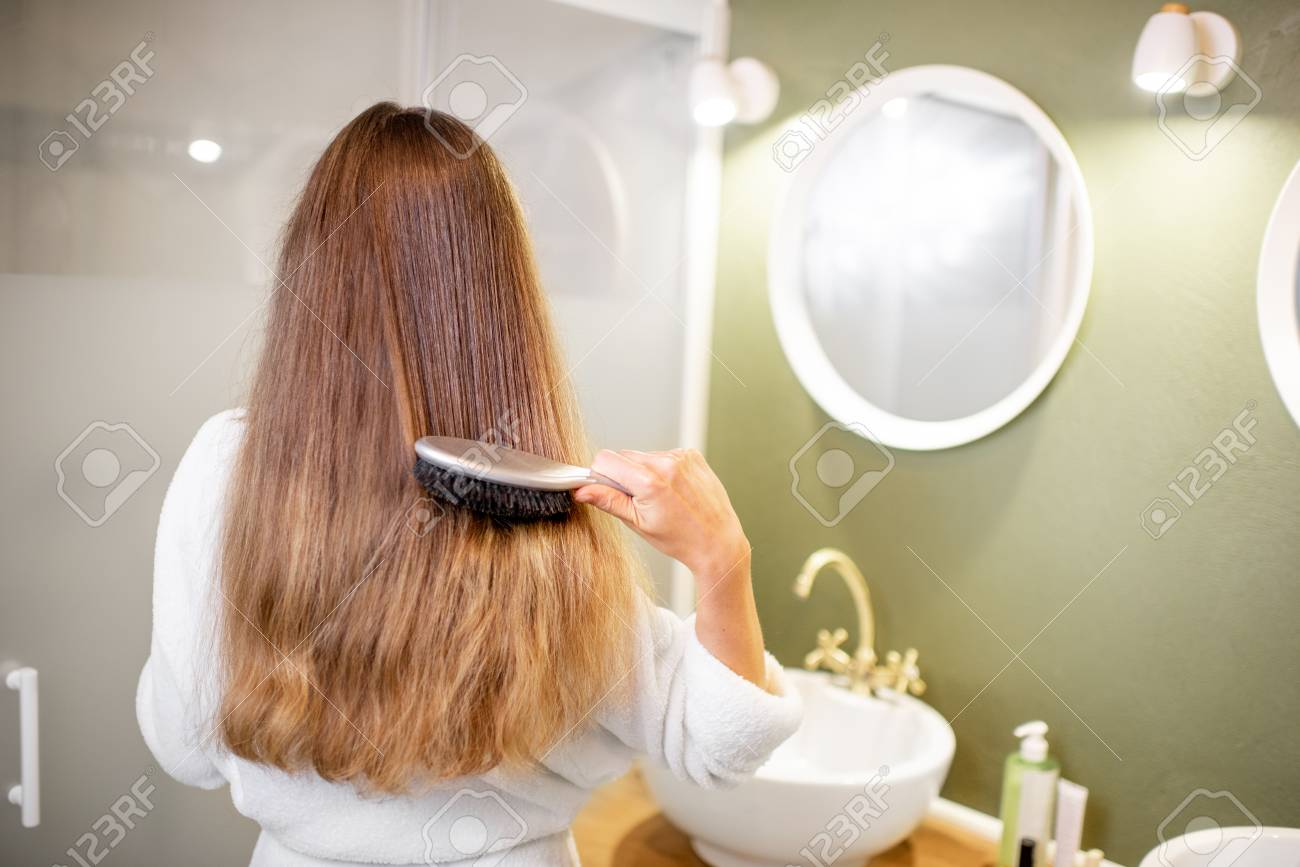 Woman in bathrobe combing hair with brush in the bathroom, rear view - 113338199