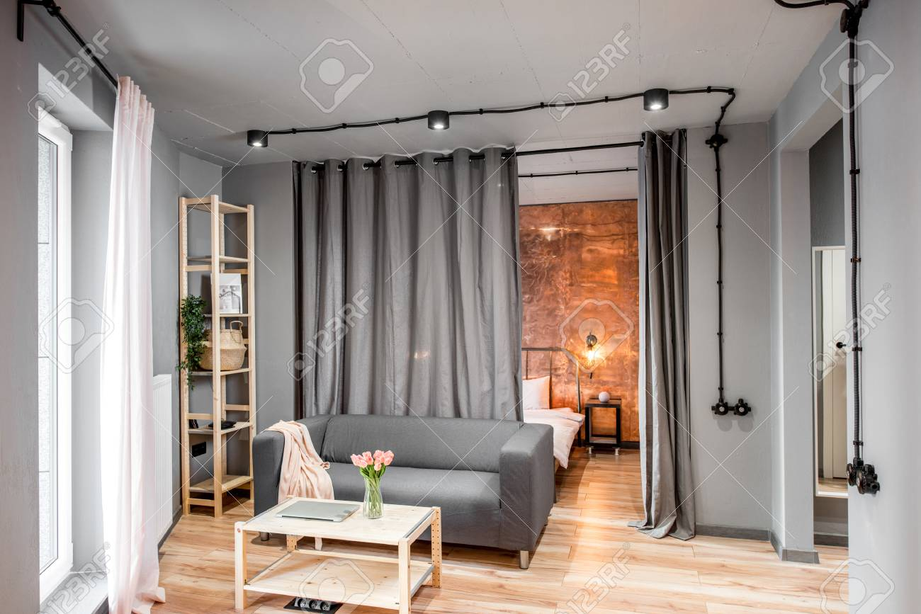 Modern living room in loft style made in grey colors with sofa..