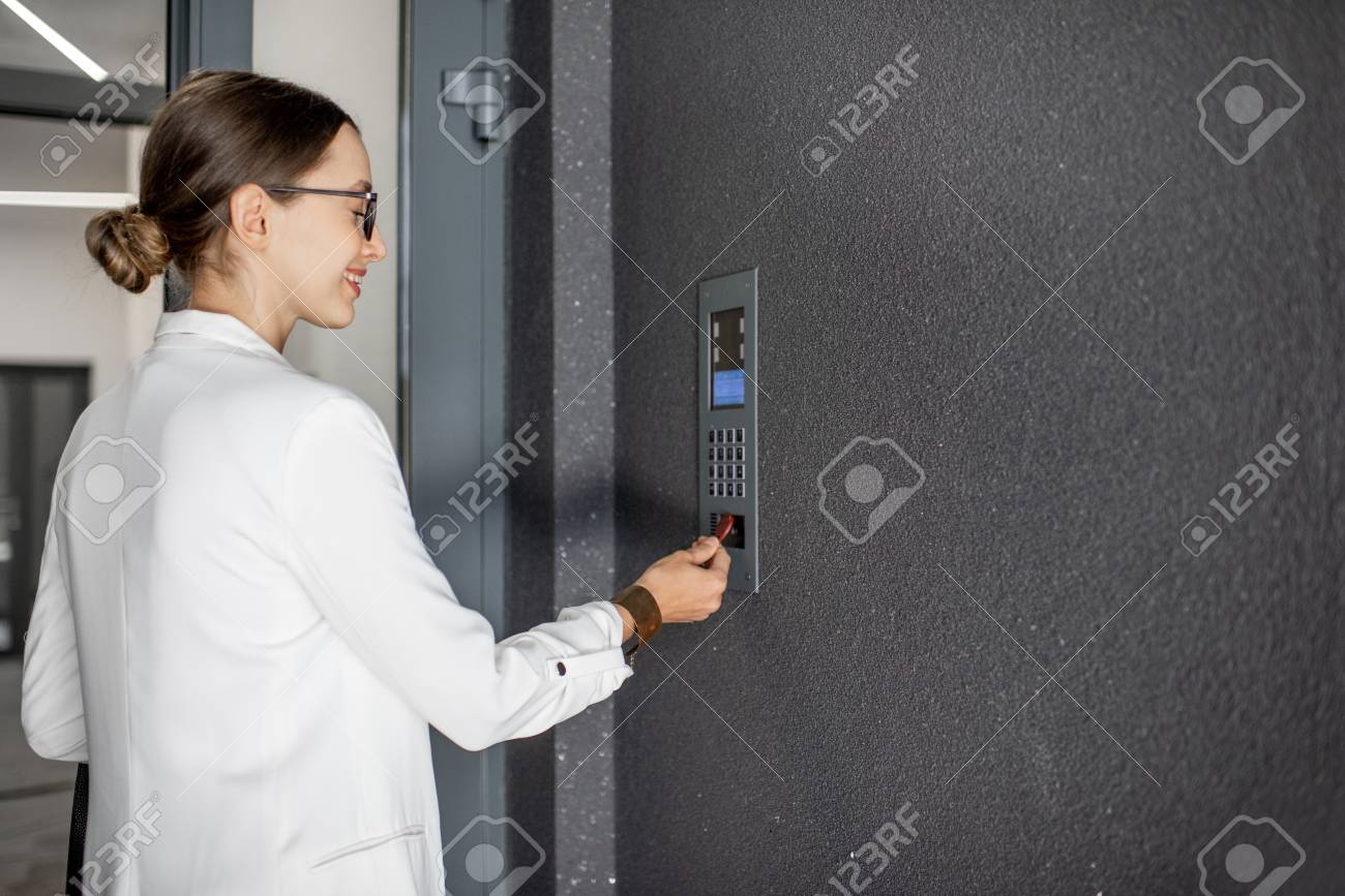 Young business woman in white suit touching the intercom with keychain opening the door of residential modern building - 113401396