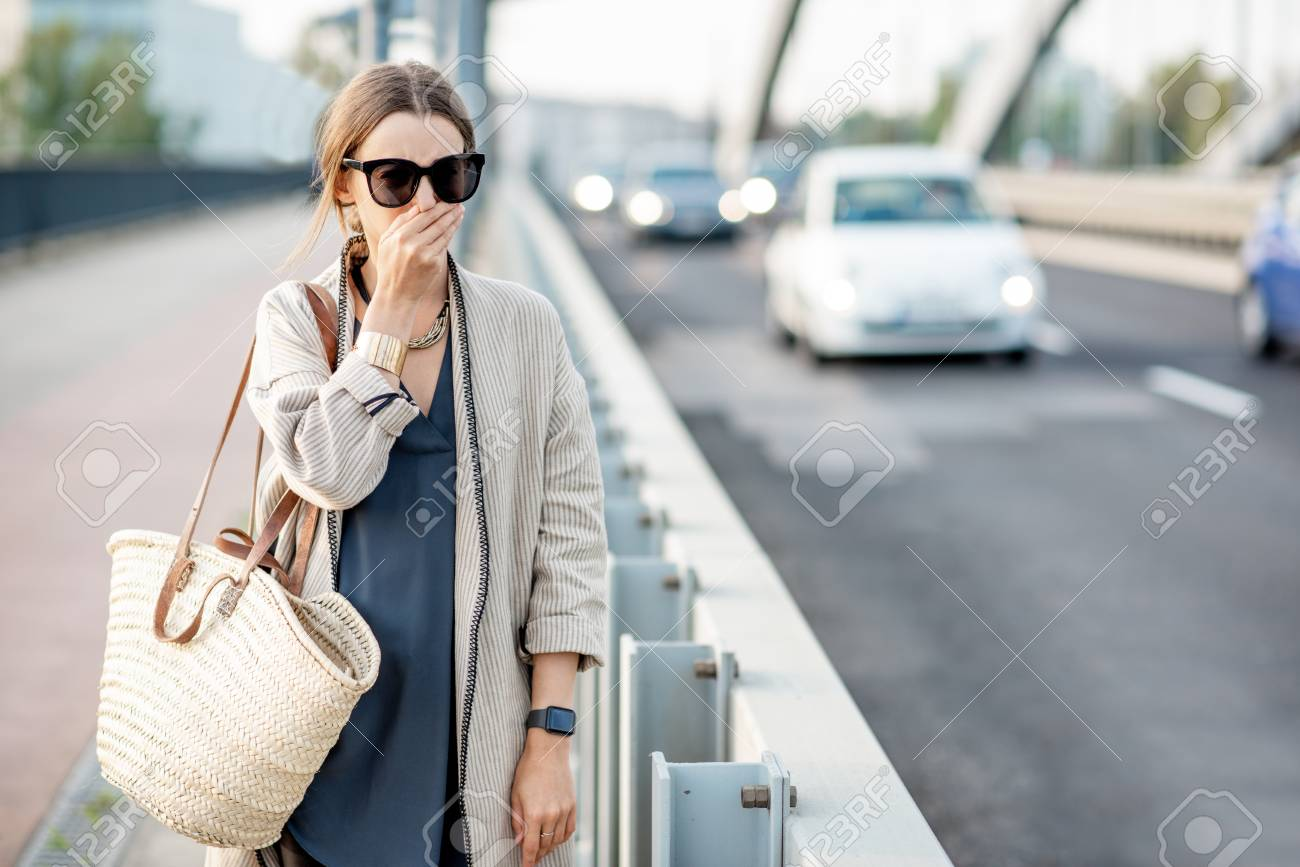 Woman closing her nose feeling bad because of the air pollution on the bridge with traffic in the city - 113402099