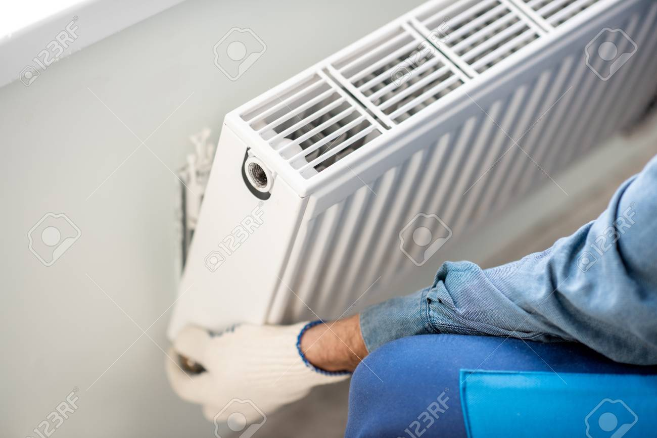 Workman mounting water heating radiator on the white wall indoors, close-up view - 112134302