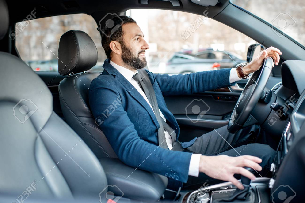 Handsome bearded businessman dressed in the suit driving a car in the city - 112372574