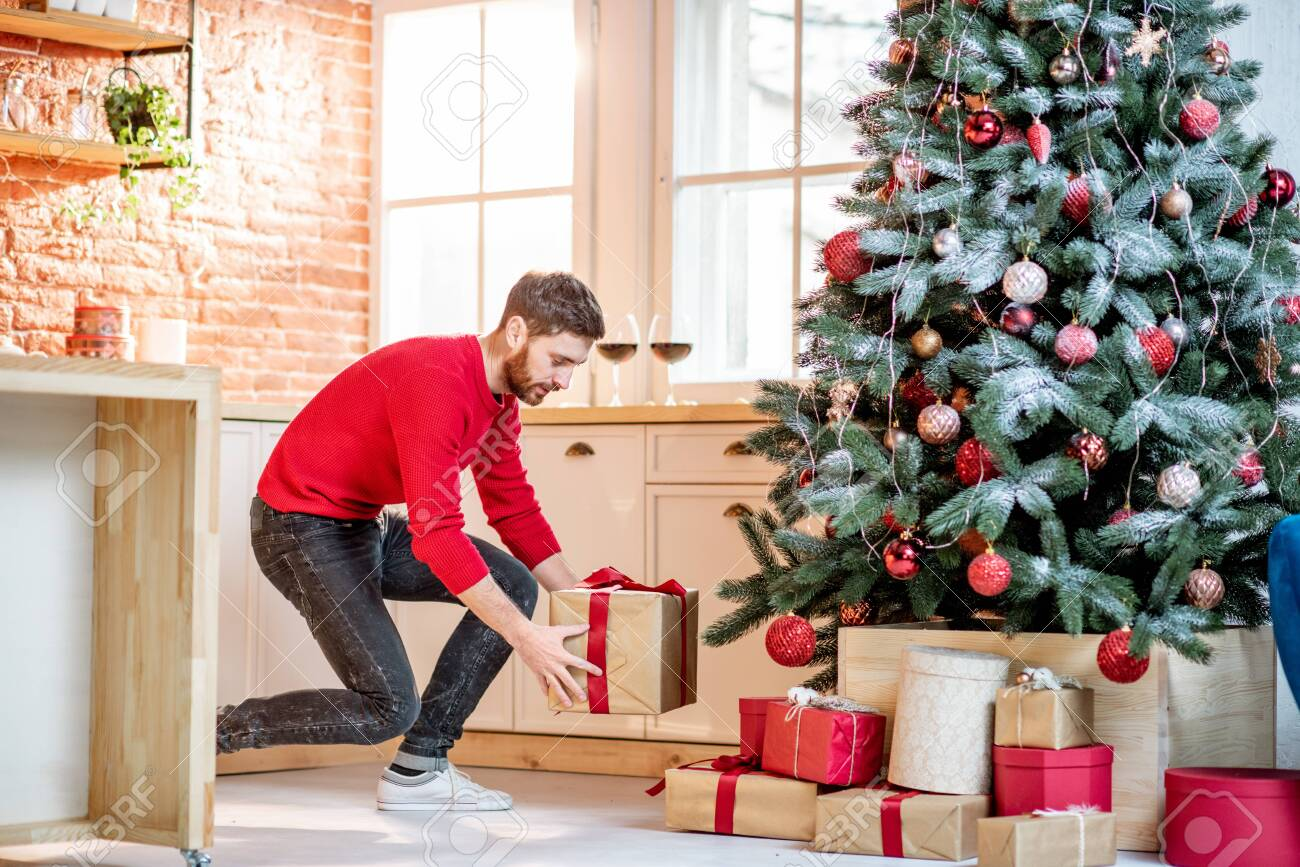 Man putting gifts under the Christmas tree preparing for a New Year holidays at home - 113404328