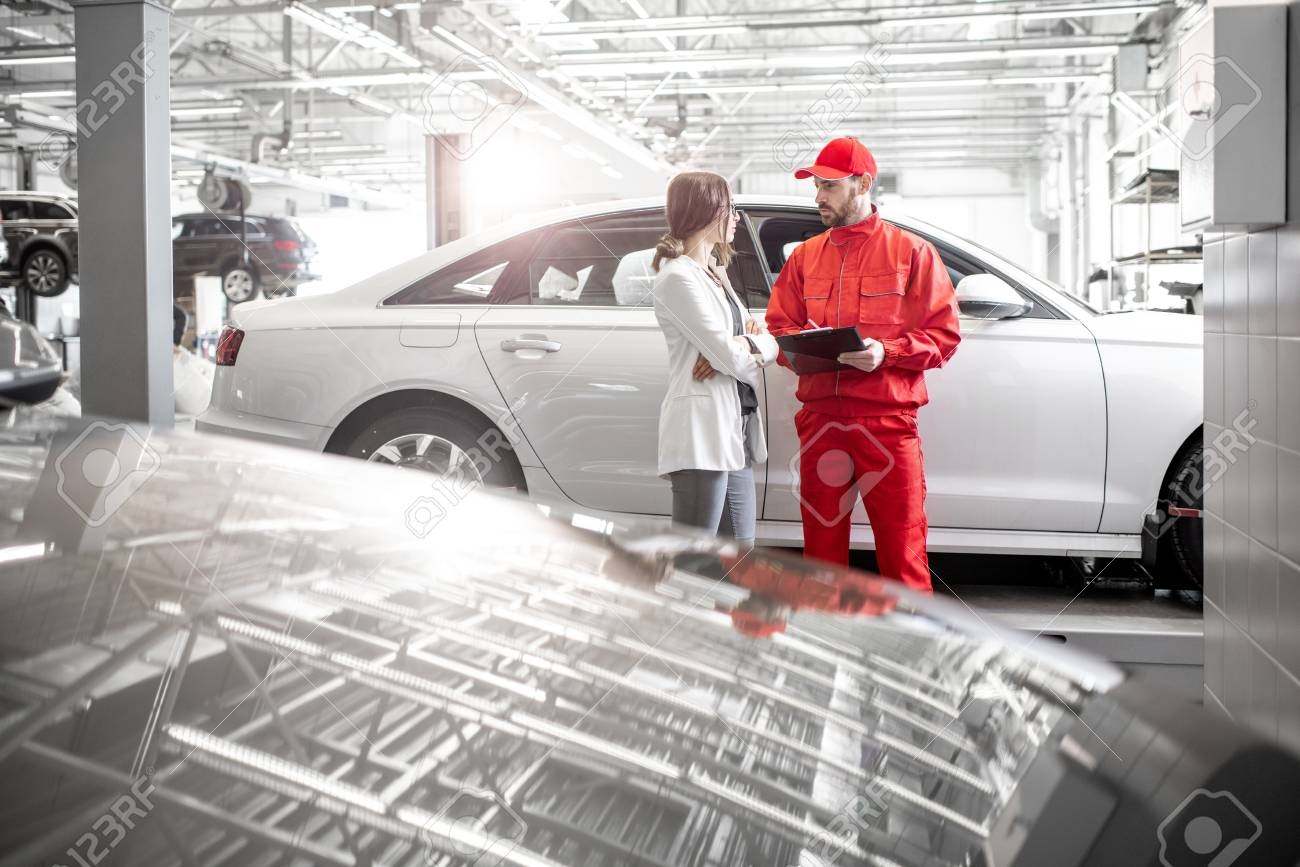 Young woman client with auto mechanic in red uniform at the car service. Wide angle view with copy space - 113406163