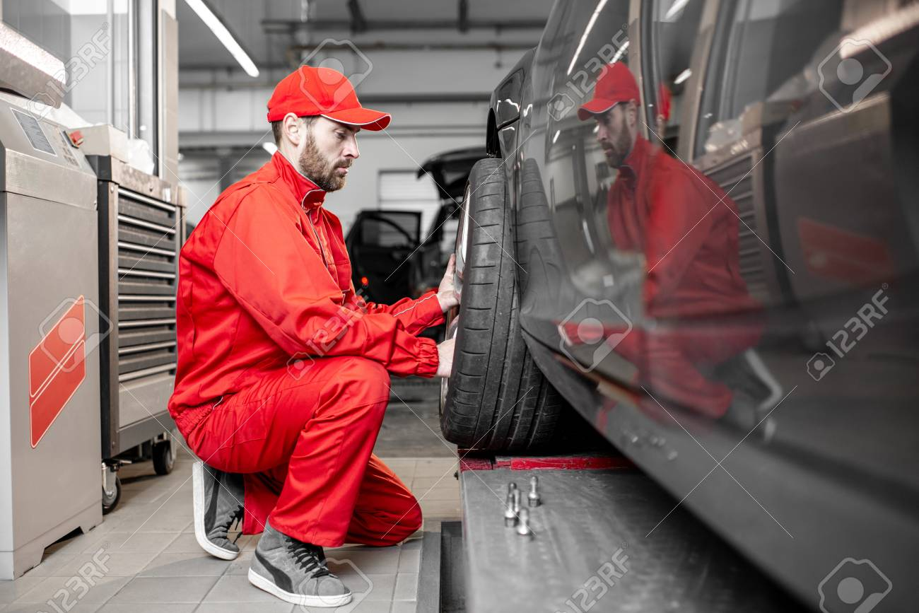 Two car service workers in red uniform changing wheel of a sport car at the tire mounting service - 114132905