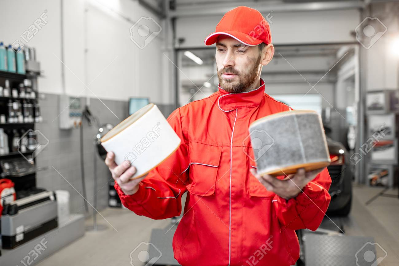 Auto mechanic in red uniform holding new and used air filter standing at the car service - 114132912