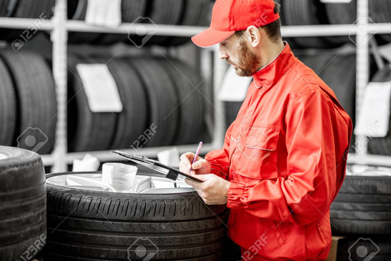 Worker or salesman in red uniform filling some documents checking goods in the warehouse with car tires - 114133682