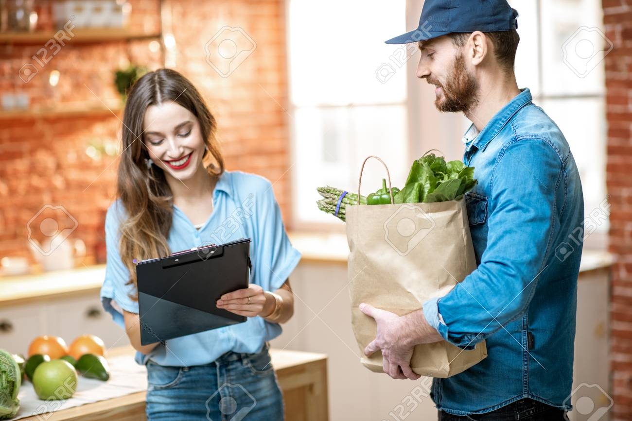Courier service worker delivering fresh food to a happy woman client signing some documents on the kitchen at home - 114133789