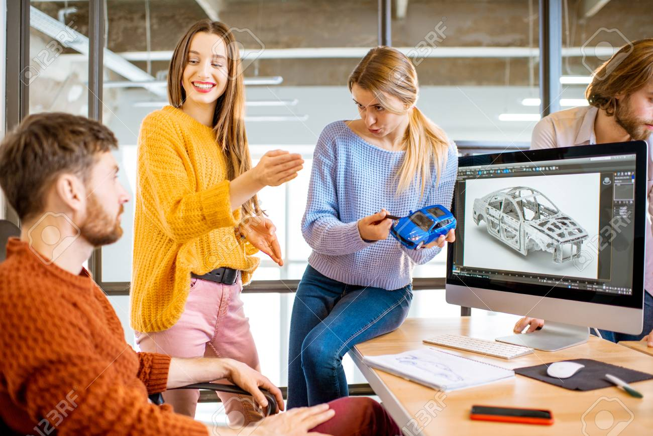 Group of young creative coworkers designing a car model at the working place with computers in the modern office interior - 114779924