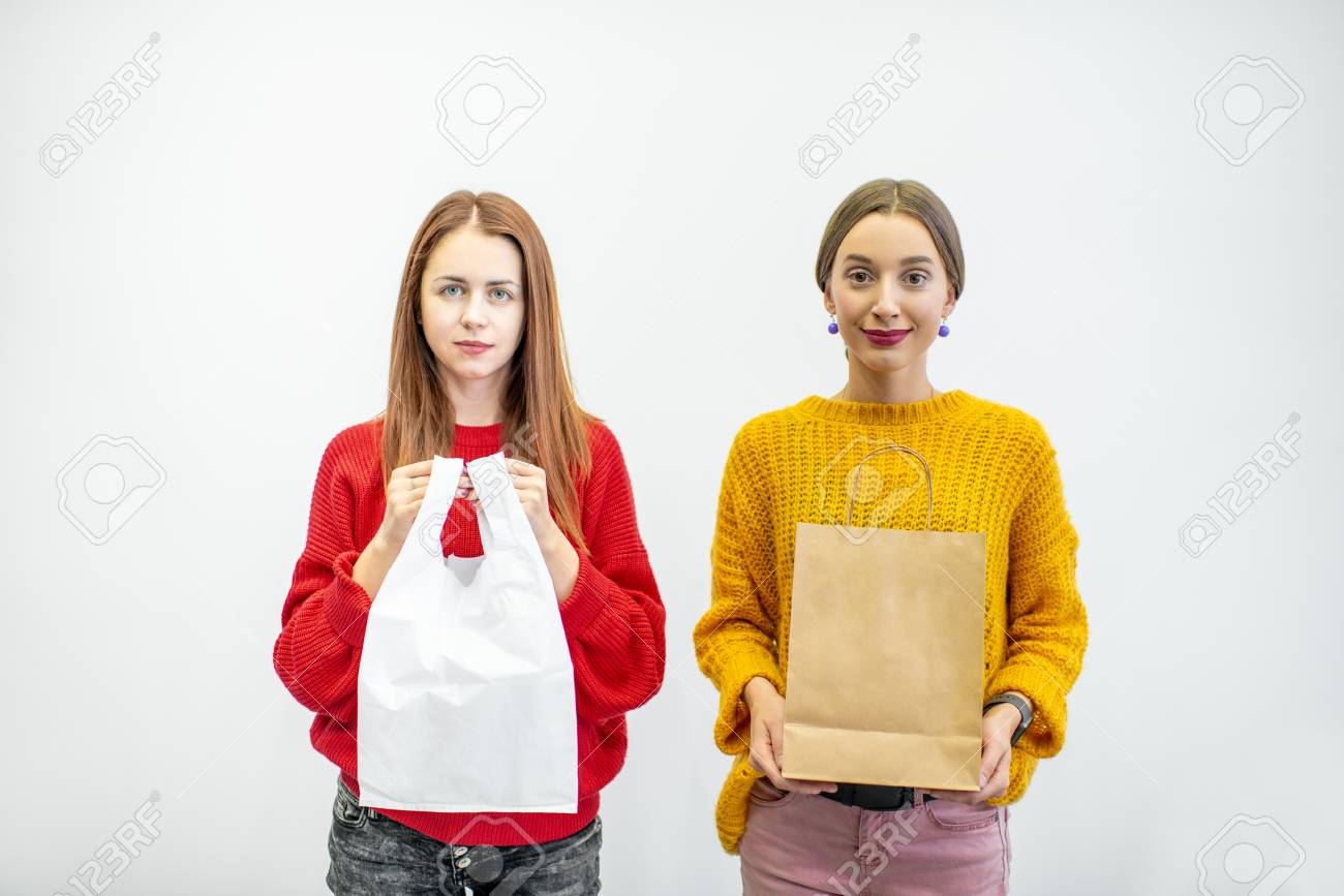 Portrait of a two women holding plastic and paper bags standing on the white background. Ecological in contrast to non recyclable packaging concept - 114781026