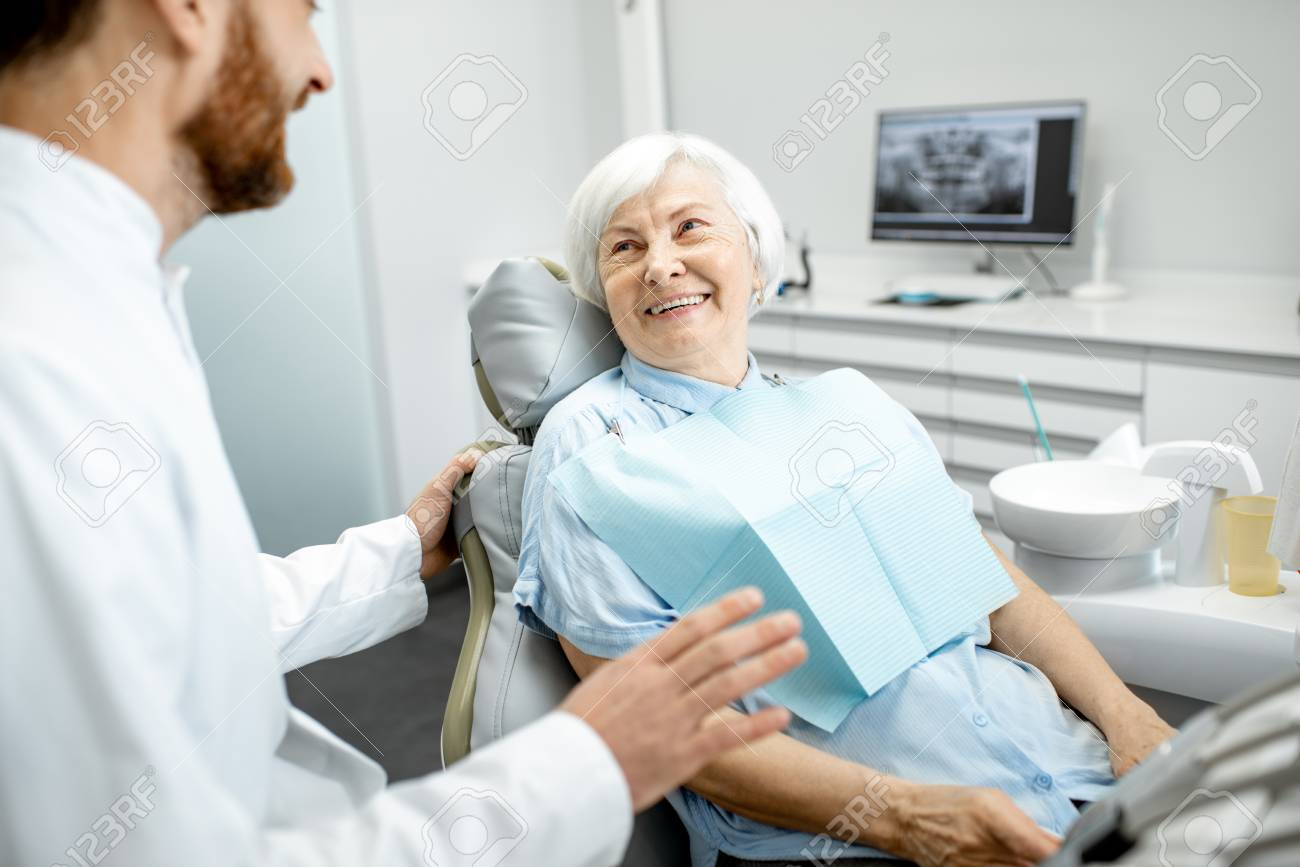 Beautiful elder woman with healthy smile sitting during the consultation with dentist at the dental office - 114781068