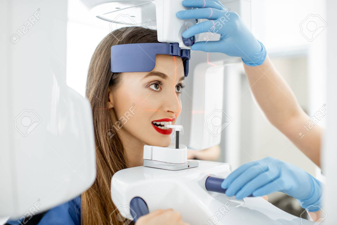 Young woman making panoramic shot of the jaw holding her face at the x-ray machine - 114781377