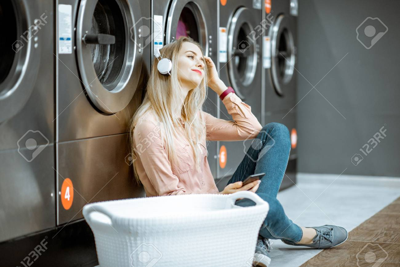 Young woman waiting for the clothes to be washed sitting on the floor and listening to the music at the self-service laundry - 115518762