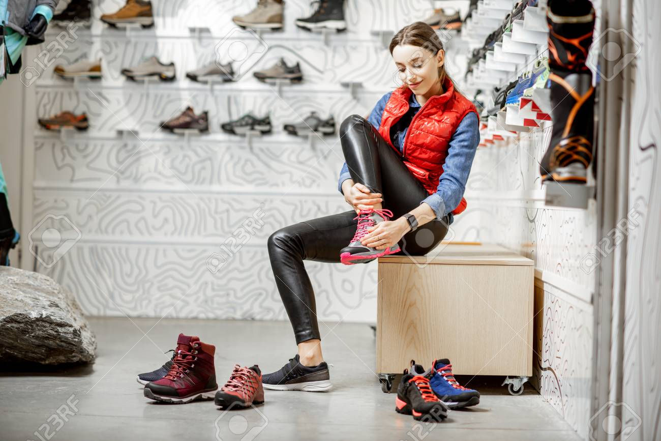 Woman trying shoes for mountain hiking sitting in the fitting room of the modern sports shop - 115281241