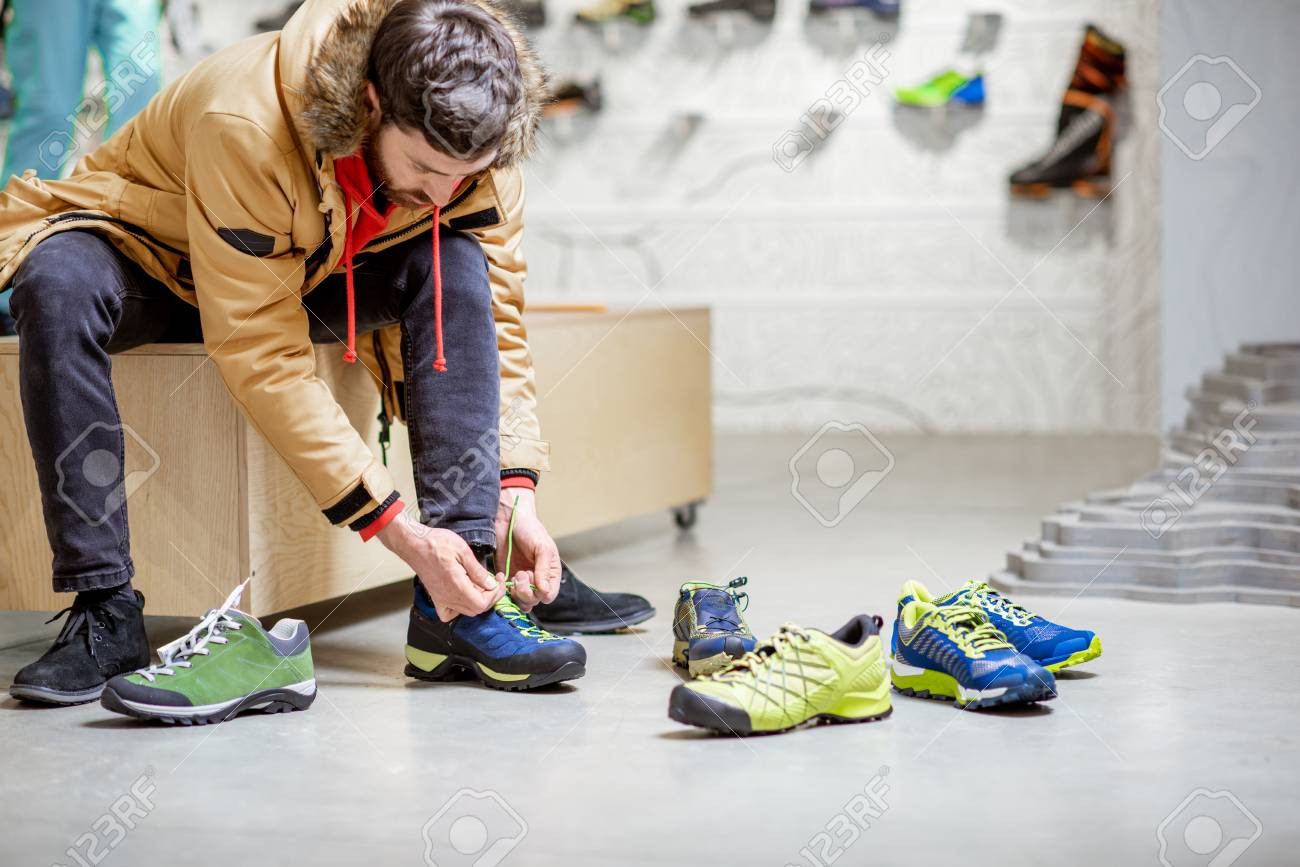 Man in winter jacket trying shoes for mountain hiking sitting in the fitting room of the modern sports shop - 115281255