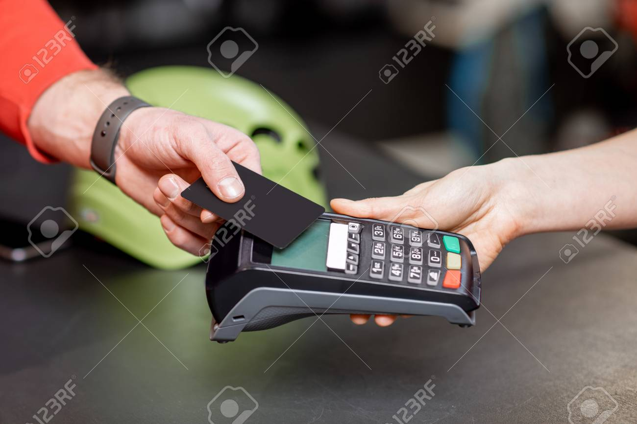Man making purchase with bank card and cash register at the counter of the sports shop, close-up view - 115281473