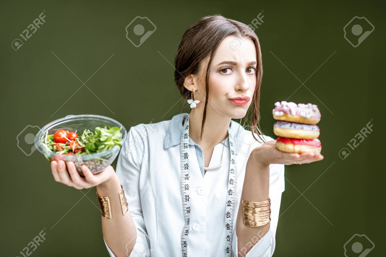Young woman nutritionist looking on the donuts with sad emotions choosing between salad and unhealthy dessert on the green background - 115514594