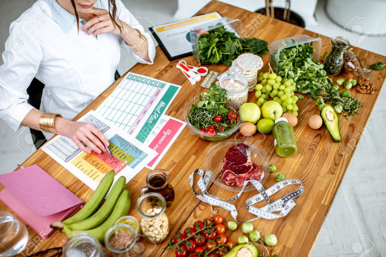 Dietitian writing a diet plan, view from above on the table with different healthy products and drawings on the topic of healthy eating - 115514645