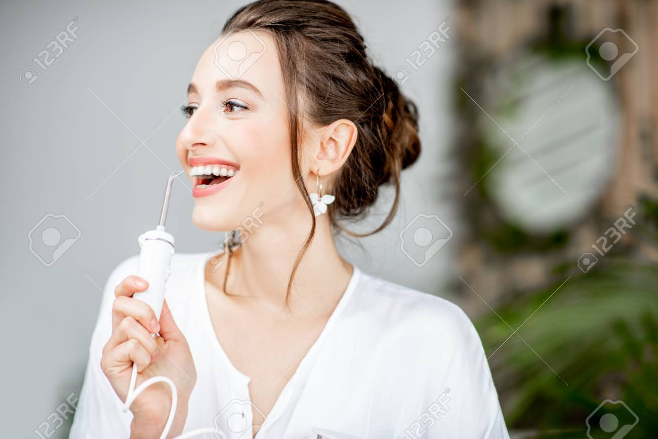 Portrait of a beautiful woman with shiny smile holding irrigator tool for teeth cleaning in the bathroom - 116442289