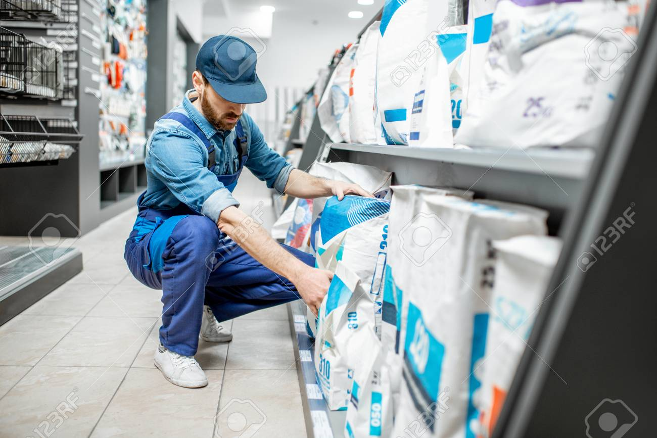Workman in blue overalls taking a bag with construction mixture, buying materials for repairing in the building supermarket - 116650655
