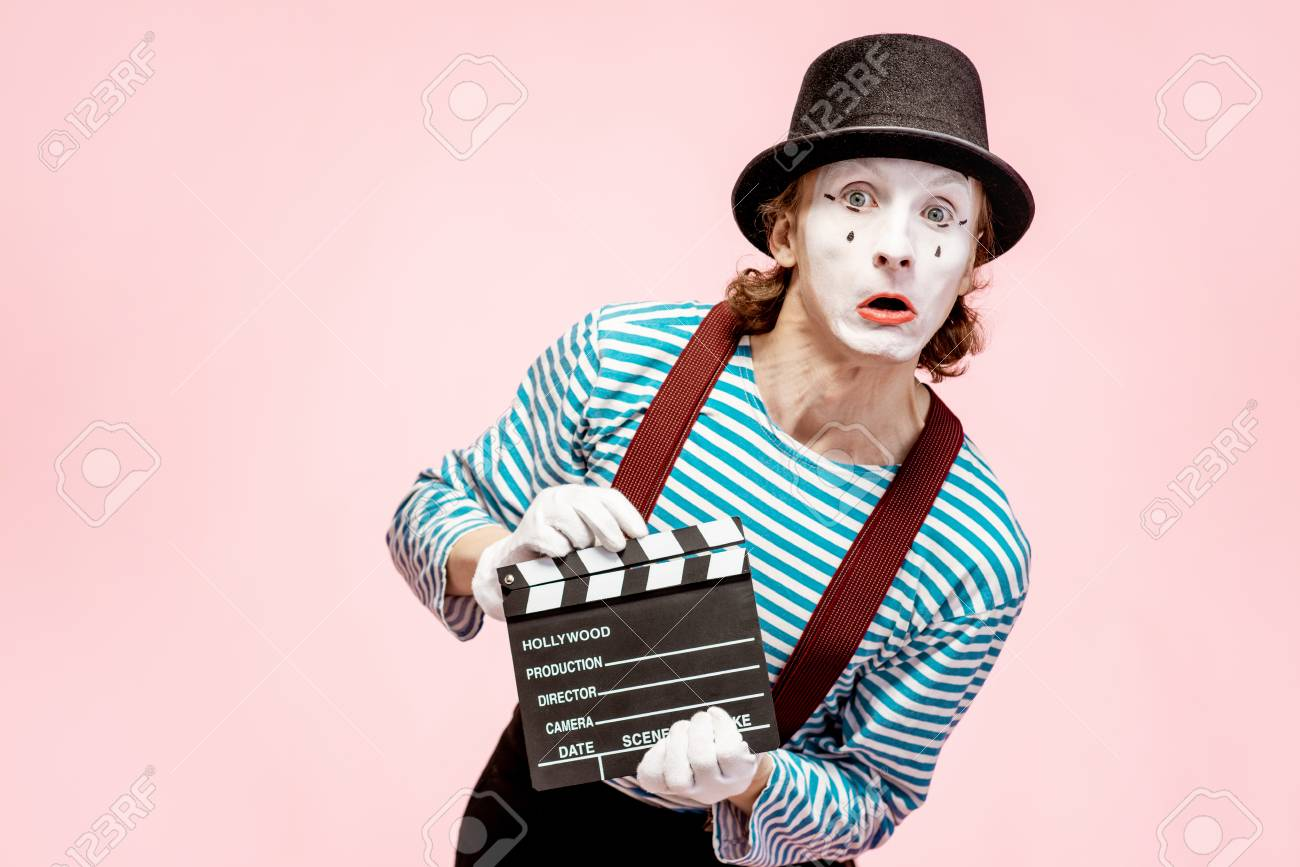 Portrait of an actor as a pantomime with cinematography clapperboard on the pink background - 118134545
