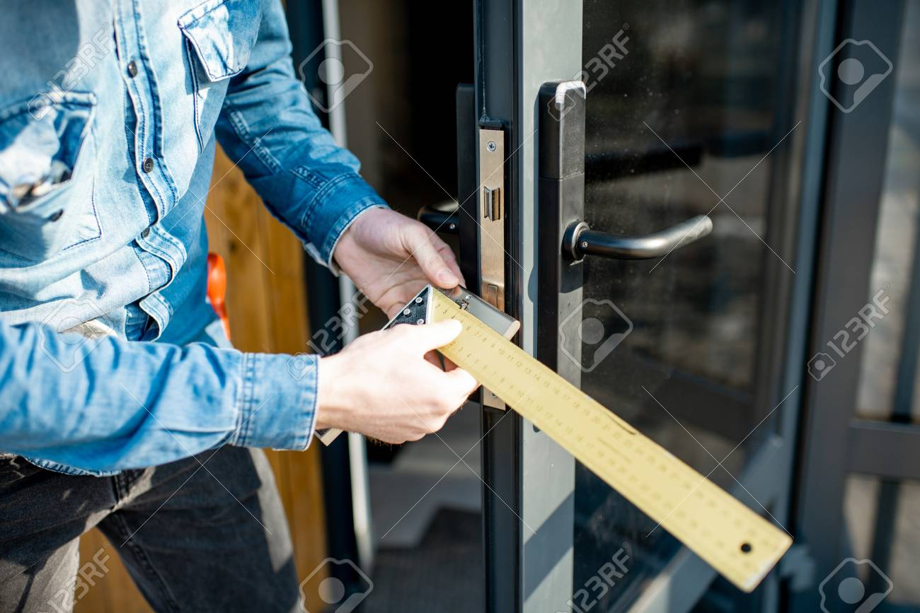 Man changing core of a door lock of the entrance glass door, close-up view with no face - 118140082